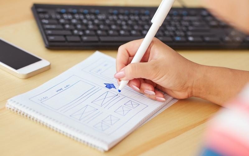 web designer sketching in notebook